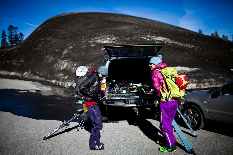 Jenna Murano, left, and Rachel Rainey leave for a backcountry tour in front of a pile of old snow covered with volcanic dust at Mammoth Mountain.