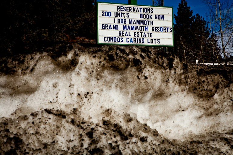 A sign advertising vacation rentals behind an old snow bank in Mammoth Lakes.