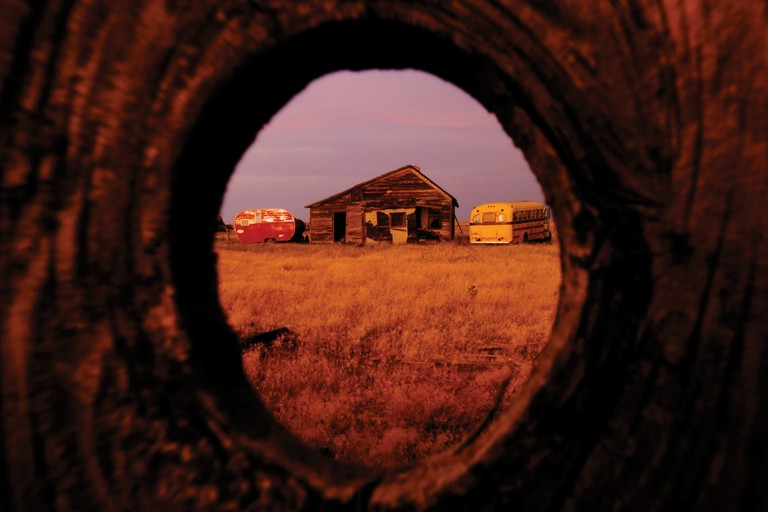 Seen through a knothole in an old structure, the sun sets on the remnants of Vananda, which is listed on the National Register of Historic Places and has kept its place on the map despite being uninhabited.