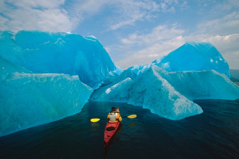 A sea kayaker approaches an iceberg at Tracy Arm in the Summer Fords-Terror Wilderness Area of the Southeast Alaska portion of the Inside Passage.