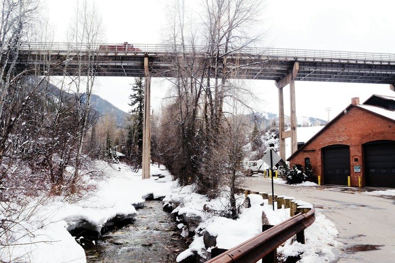 A section of Castle Creek running next to a city garage in Aspen, Colorado. The 1893 building was the city's first hydropower plant. A proposed new hydro turbine, which would use water diverted from upstream and release it back into the creek here, faces community opposition.