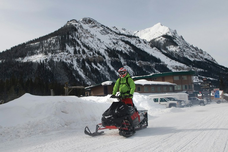 A snowmobiler rides out of Cooke City, Montana, on the northeast boundary of Yellowstone National Park. Park officials announced delays in plowing roads due to the sequester, causing local business owners to worry about a drop in spring visitors.