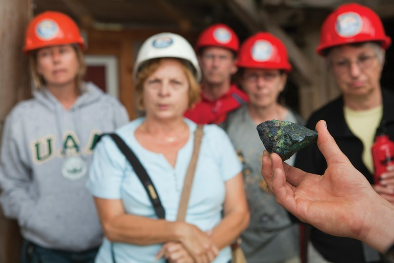 A tour guide holds out a sample of copper ore during a tour of the mill building in Kennecott, Alaska, site of the historic Kennecott Copper Mine.