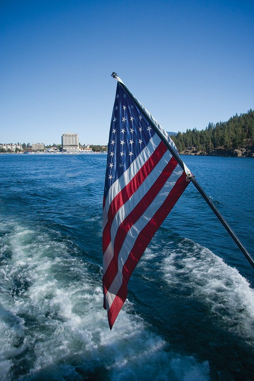 An American flag flies from the stern of a tour boat off the shoreline of Coeur d'Alene, Idaho.