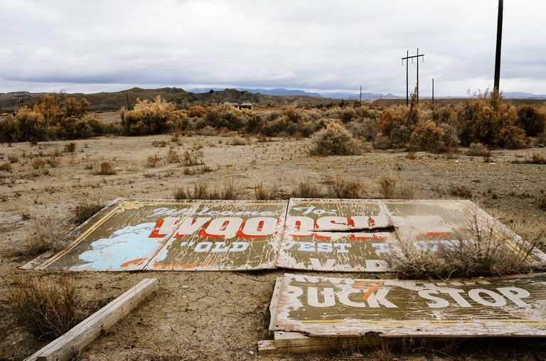 A sign that once drew travelers off the highway to the geyser in Woodside, Utah, now lies in the weeds.