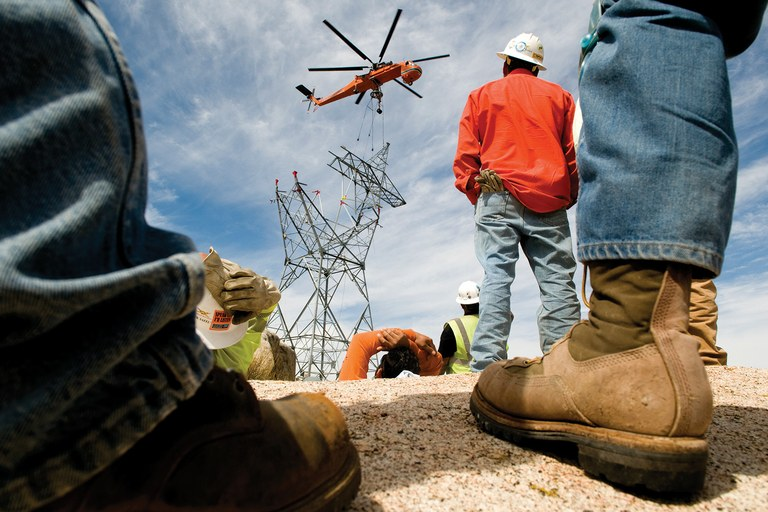 Contractors watch last April as a helicopter places a lattice tower for the Sunrise Powerlink, the controversial 117-mile, 500-kilovo