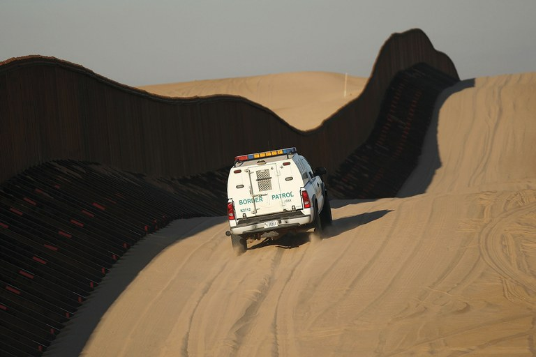 A Border Patrol vehicle makes tracks in the denuded desert at the border fence near Yuma, Arizona.
