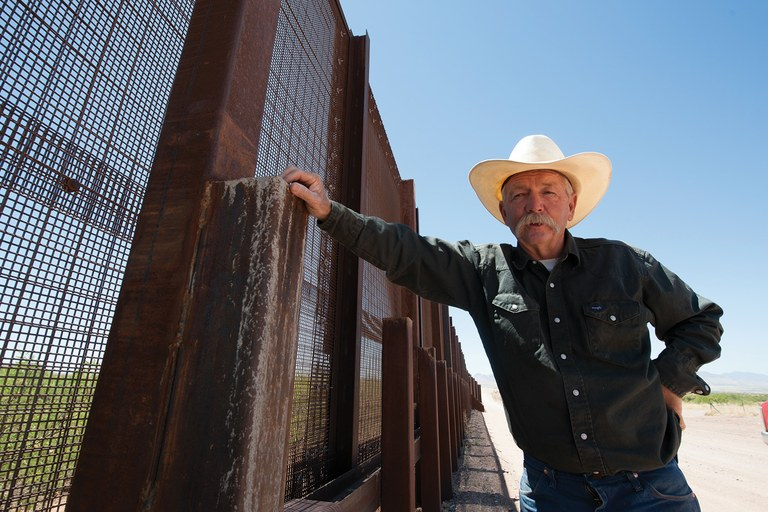 John Ladd, a fourth-generation Arizona cattle rancher, at the border wall that runs along his property.