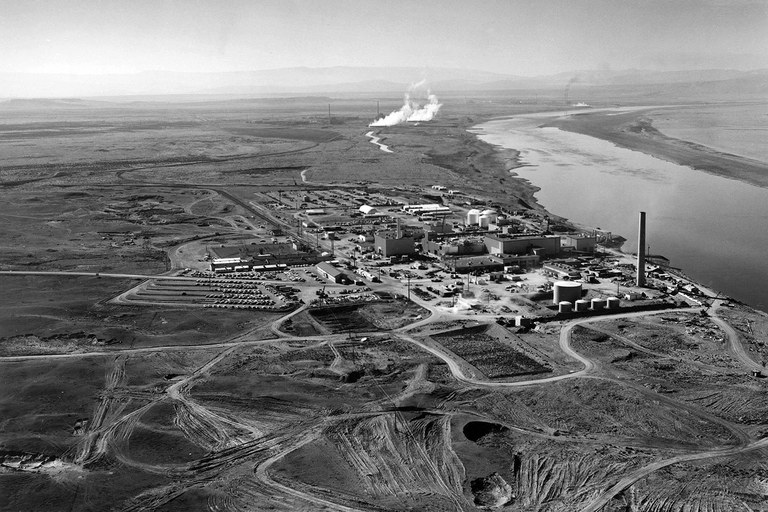 Nuclear reactors lined the banks of the Columbia River at the Hanford Site, shown in 1960. The N Reactor is in the foreground, with the twin KE and KW Reactors in the immediate background. The historic B Reactor, the world's first plutonium production reactor, is visible in the distance.