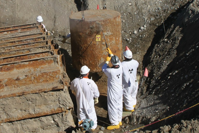 Cleanup workers survey a tank buried for years in a Hanford trench, readying it for removal.