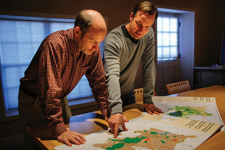 "John Horning, far left, and Bryan Bird study greater Gila bioregion land ownership maps at the WildEarth Guardians office in Santa Fe, New Mexico. The maps identify land leased by ""wolf-friendly ranchers"" as well as areas the group has targeted for permit retirement."