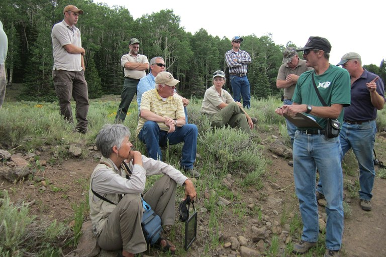 O'Brien, seated front, and Hopkin, yellow shirt, at a briefing before a tour of the Box Creek fire and fencing project on the Fishlake National Forest.