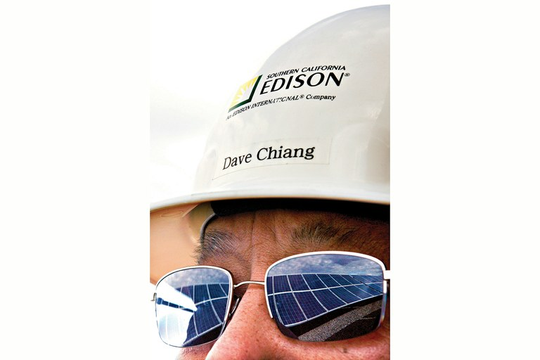 Solar modules are reflected in the sunglasses of David Chiang, a project manager at Southern California Edison's Porterville solar array.