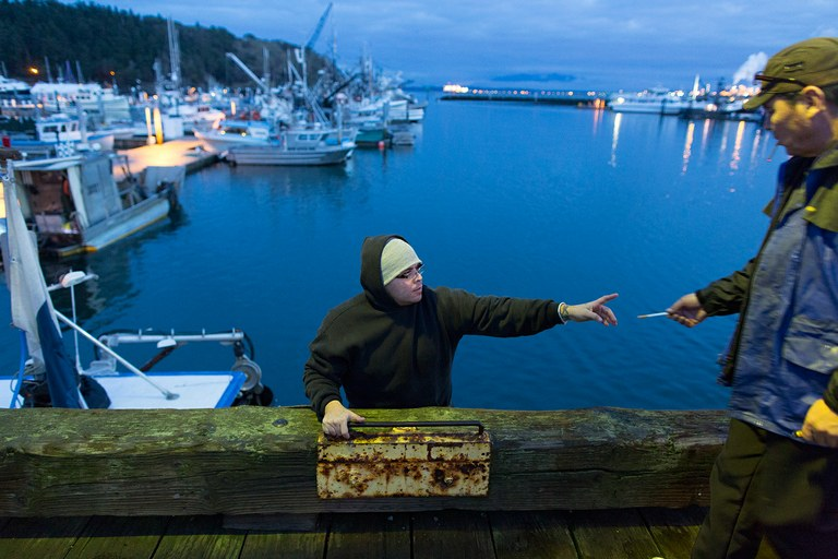 Deckhand Jason Paul takes a cigarette from a sea urchin buyer at a marina in Anacortes, Washington.