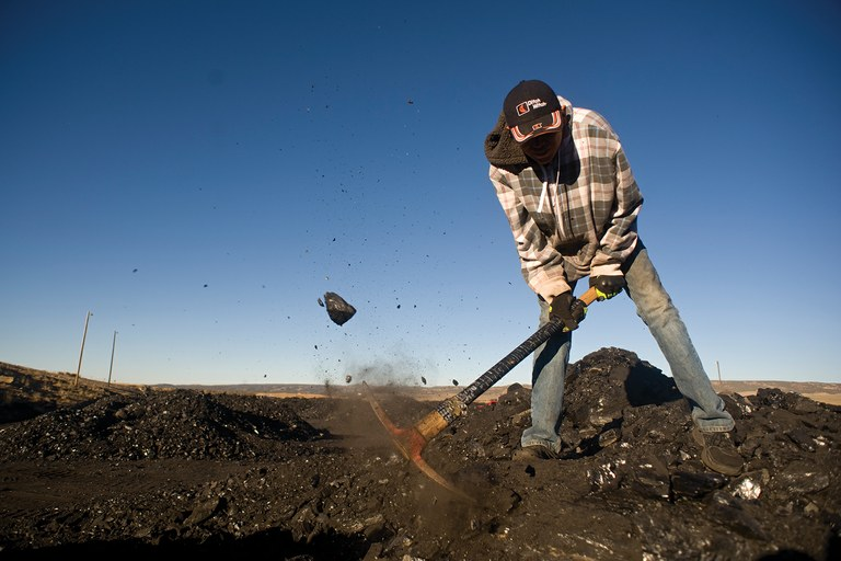 Navajo Keanu Israel loosens coal in a pile at the public load-out of the Kayenta Mine in Black Mesa, Arizona. He and his brother were helping their grandparents haul a truckload to heat their home.