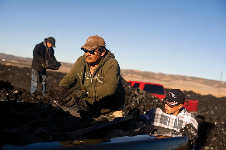Lloyd Israel and his two grandsons, Keanu and Garrick, sort coal at the public load-out facility, part of the Kayenta Mine in Black Mesa, Arizona. The family uses coal to heat their home.