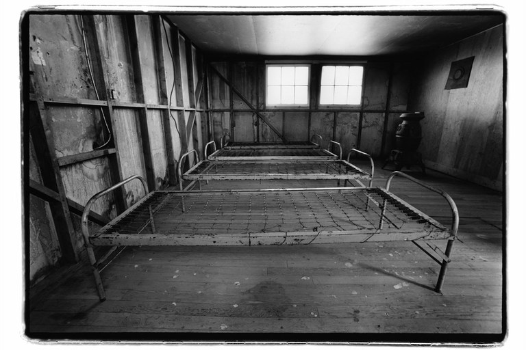 Bedframes remain in a barrack at Minidoka.