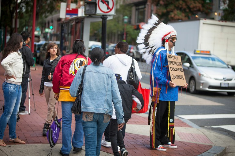 Deal uses provocative signs and stereotypical but inauthentic Indian garb to trigger reactions as part of his performance art project, titled The Last American Indian on Earth, working mostly in Washington, D.C.