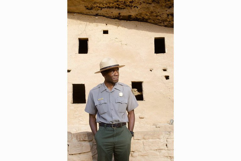 Mesa Verde National Park superintendent Cliff Spencer stands in front of Spruce Tree House, a popular site in the park. Minorities are under-represented both in the Park Service's workforce and among its visitors.