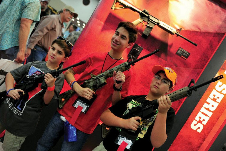 Boys pose for a photo holding Bushmaster rifles during a National Rifle Association convention in Houston, Texas.