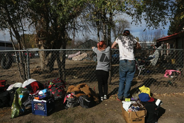 A woman and her husband discuss housing options while they stand on the street with their family's belongings after leaving the place they were staying because of a physical altercation. Meanwhile, the local authorities had come to arrest the owners of the house, where as many as 10 people had been staying, and where Josh Flaharty says he used to stay and get drugs. (Brooke Warren/High Country News)