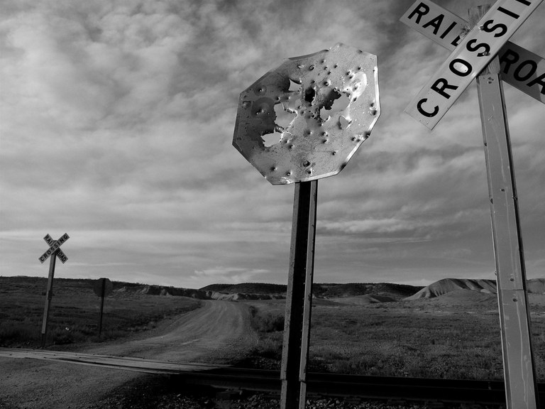 Shot-up stop sign at the crossroads