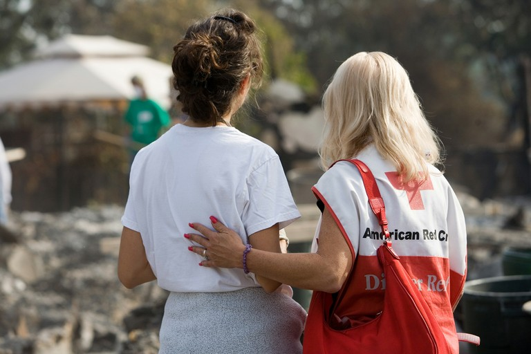 A Red Cross volunteer comforts the sister of a fire victim while friends and volunteers sift through the residents home searching for valuables after a 2007 fire in Rancho Bernardo, California.